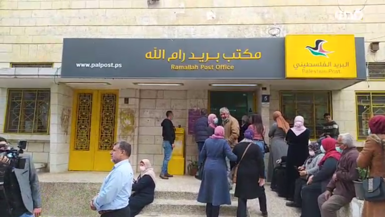 Released prisoners and the families of prisoners in Israeli jails wait in line at a post office bank branch in Ramallah (QudsN Facebook page, April 6, 2021).
