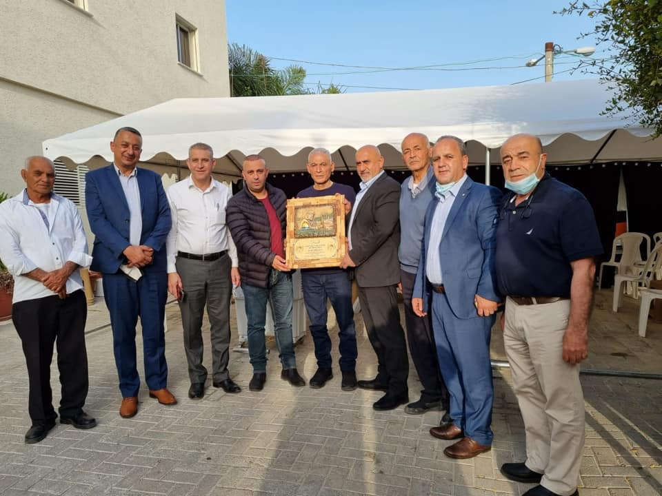 Jenin district governor Akram al-Rajoub at the home of terrorist operative Rushdi Abu Mukh. Abu Mukh holds the plaque and al-Rajoub is to his left (wearing a suit) (Akram al-Rajoub's Facebook page, April 7, 2021).
