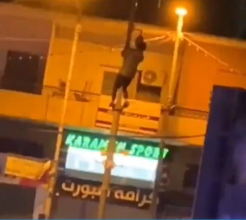 A young Palestinian climbs a pole to vandalize an Israeli police security camera (Palinfo Twitter account, April 24, 2021).