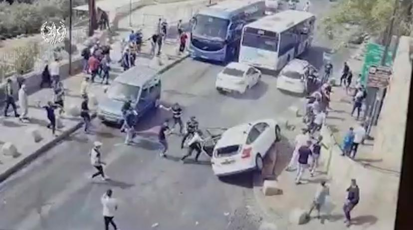 The attack and the driver defended by a policeman with drawn gun (Israel Police Force spokesman's unit, May 10, 2021).