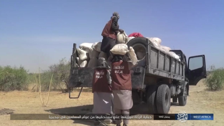 """Truck loaded with food bags to be distributed. ISIS operatives wearing vests with the inscription, """"Islamic State – Zakat."""""""