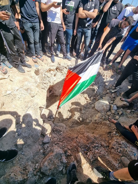 A rocket crater with Palestinian flag (Twitter account of Liam Baloum, May 15, 2021).