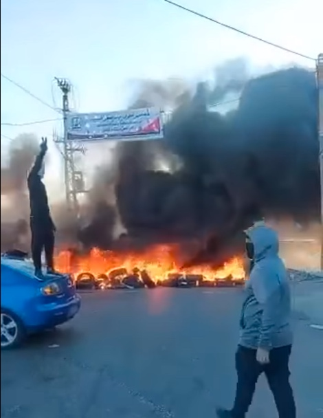Masked Palestinians set tires on fire at the entrance to Anata, north of Jerusalem (QudsN Facebook page, May 18, 2021).