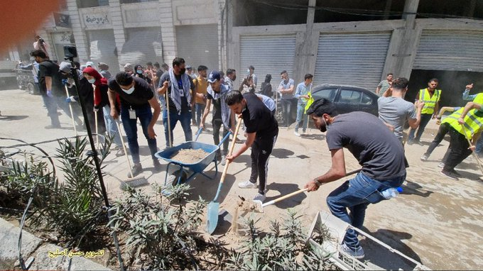 Gazan volunteers remove the rubble and clean the streets (Twitter account of journalist Hassan Aslih, May 23, 2021).