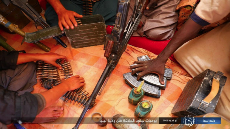 Armed operatives in Libya arranging their weapons.