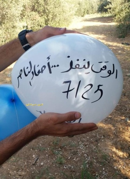 """The Popular Resistance Committees-affiliated Descendants of al-Nasser balloon-launching unit in the Gaza Strip display an incendiary balloon before launching it into Israeli territory. The Arabic reads, """"Time is running out...the Descendants of al-Nasser"""" (Twitter account of journalist Hassan Aslih, July 25, 2021)."""
