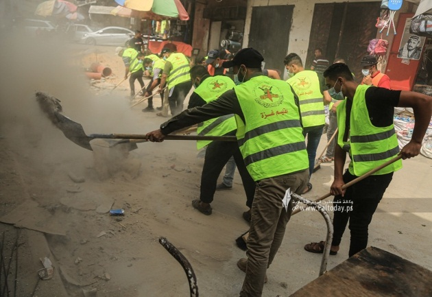 PIJ operatives wearing yellow organization vests help clear the rubble (Paltoday, July 26, 2021).