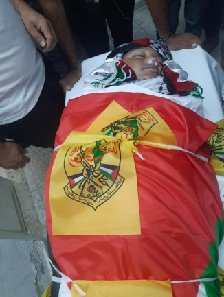 Body of Muhammad al-Alami wrapped for burial in a Fatah flag (Facebook page of the Fatah branch in northern Hebron, July 29, 2021).