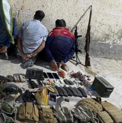 Detained ISIS operatives and some of the weapons found in their possession.