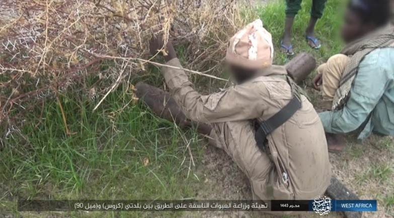 ISIS operative planting one of the IEDs against the Nigerian army.
