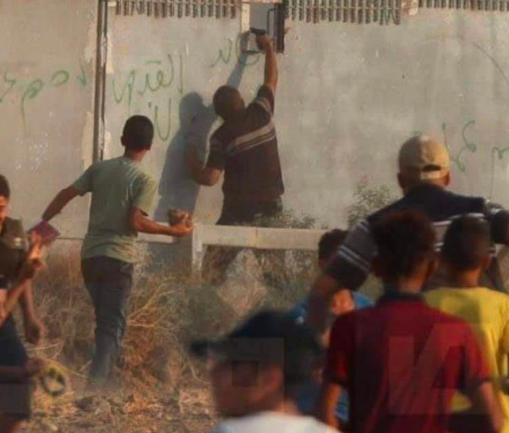 A Hamas operative shoots at a Border Police fighter through an aperture in the border security fence (Safa Facebook page, August 21, 2021).