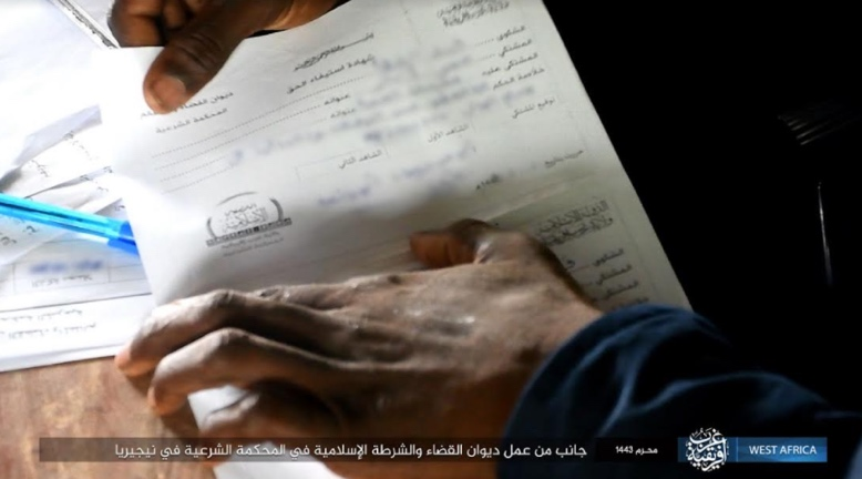 An official holding a legal document at the Bureau of Justice and Islamic Police in ISIS's sharia court in Nigeria (Telegram, August 23, 2021).