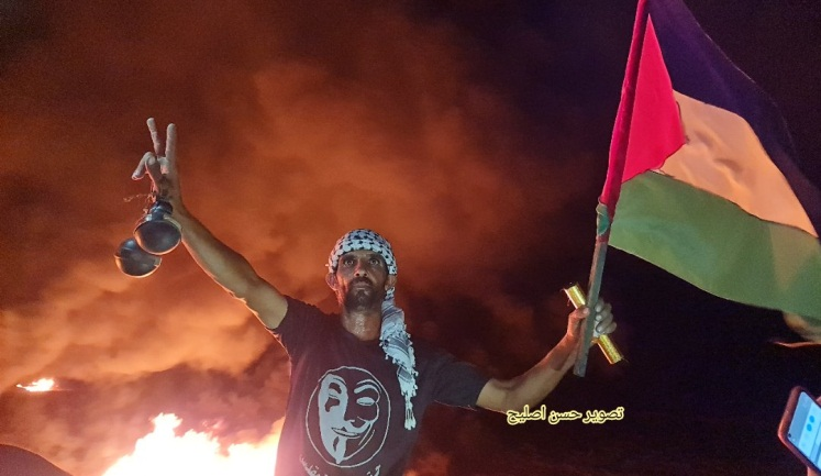 A Palestinian holds two hand grenades in one hand and a flag and a pipe bomb in the other (Twitter account of journalist Hassan Aslih, August 30, 2021).