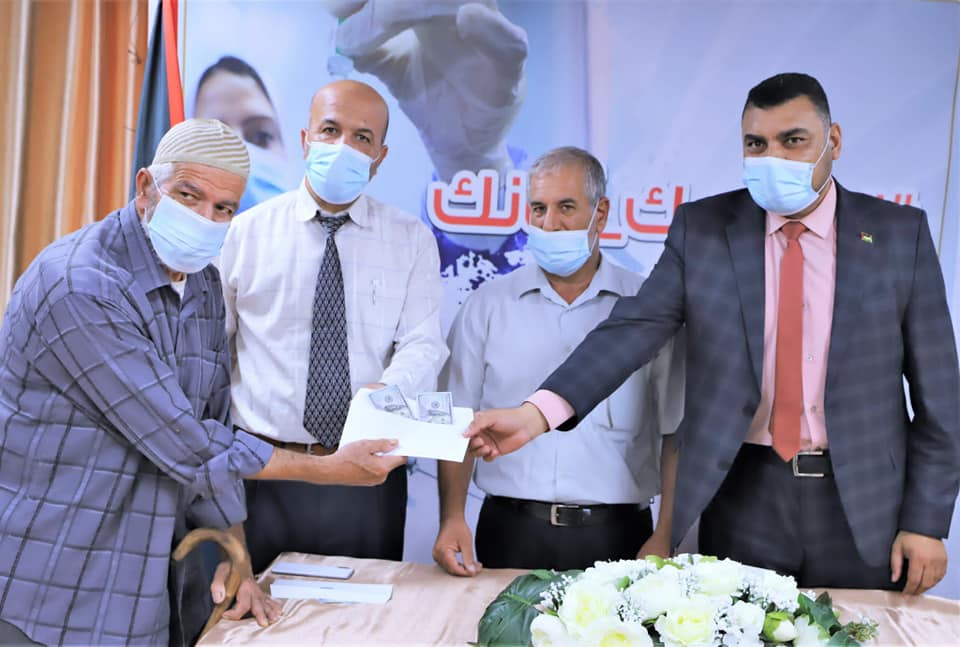 The ministry of health in Gaza gives $200 to local residents who won the vaccination lottery (ministry of health in Gaza Facebook page, August 27,2021).