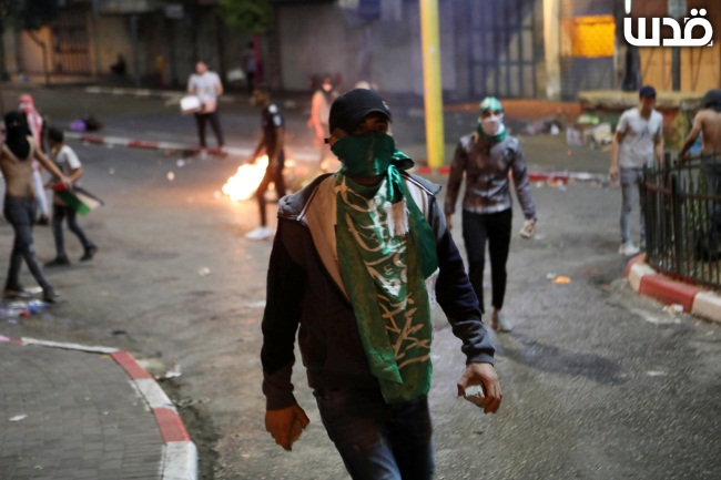 Palestinians draped with green Hamas flags riot in the center of Hebron (QudsN Twitter account, September 8, 2021).