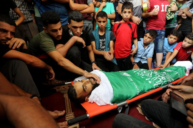 The body of Muhammad Amer wrapped for burial in the Izz al-Din Qassam Brigades flag (Twitter account of Ashraf Amara, September 30, 2021).