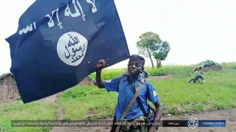 ISIS operative hoisting the ISIS flag in the village