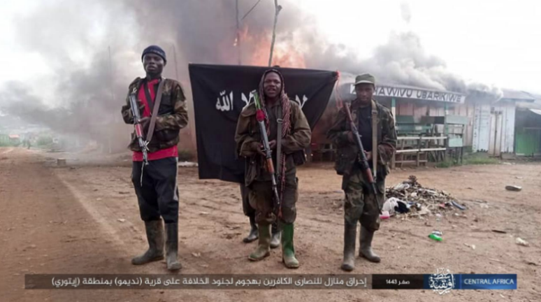 Armed ISIS operatives armed next to an ISIS flag, with the homes of Christian residents in the village going up in flames in the background (Telegram, September 13, 2021)